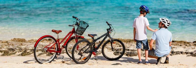 Fader och ungar på stranden med cyklar arkivbild