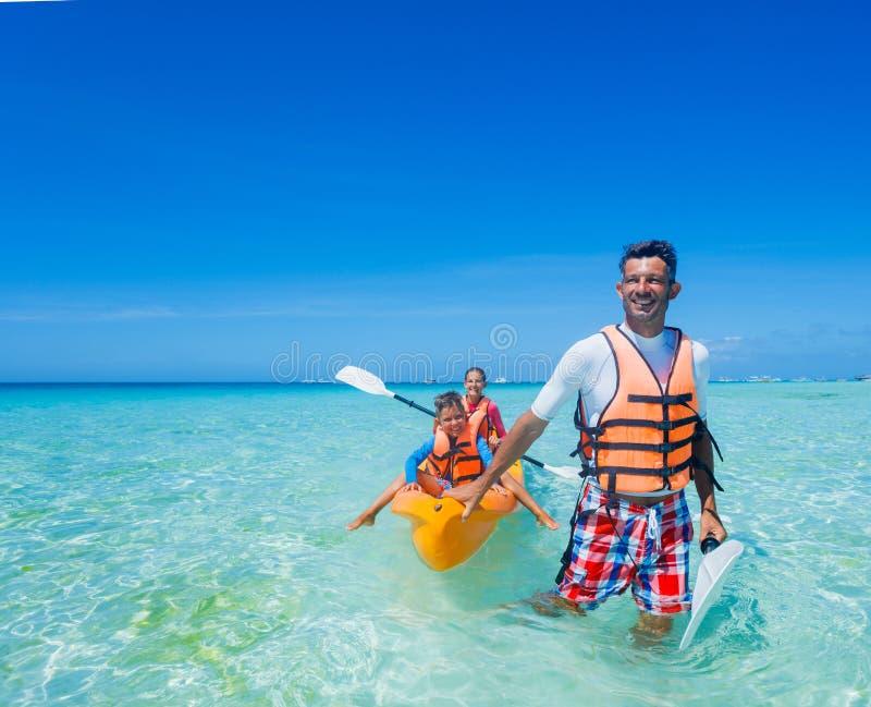 Fader och ungar som kayaking på det tropiska havet arkivbilder