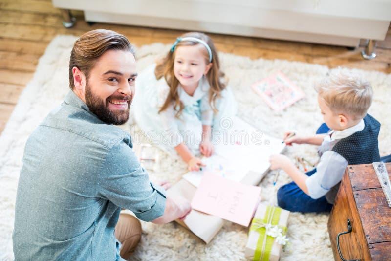 Fader och ungar som packar gåvor royaltyfri bild