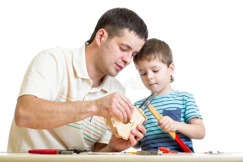 Fader- och ungebarn som tillsammans arbetar arkivfoto