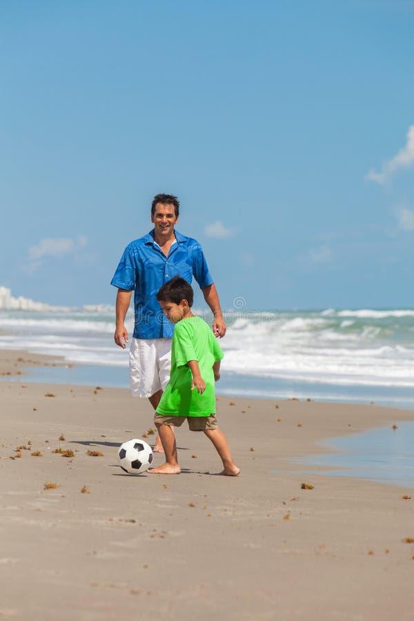 Fader Parent Boy Child som spelar fotbollfotboll på stranden royaltyfri foto
