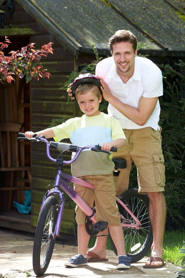 Fader Putting Saftey Helmet på son för cykelritt fotografering för bildbyråer