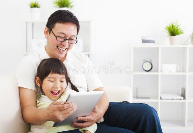 Fader som använder minnestavlaPC med lilla flickan royaltyfri foto
