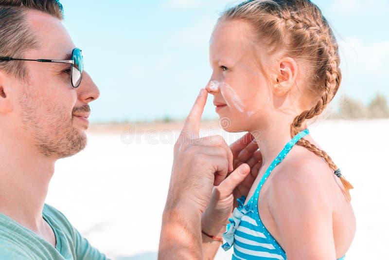 Fader som applicerar solkr?m till dottern?san fotografering för bildbyråer