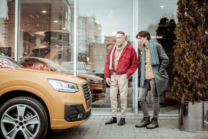 Fader som bär det röda omslaget som tänker om den köpande bilen för hans sonfödelsedag arkivbild