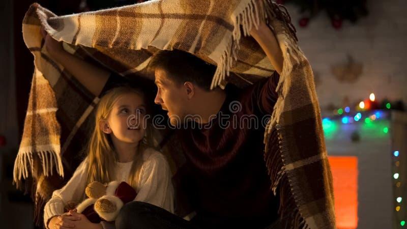 Fader som berättar den hisnande berättelsen X-mas för lilla flickan som sitter under den hemtrevliga plädet royaltyfria foton
