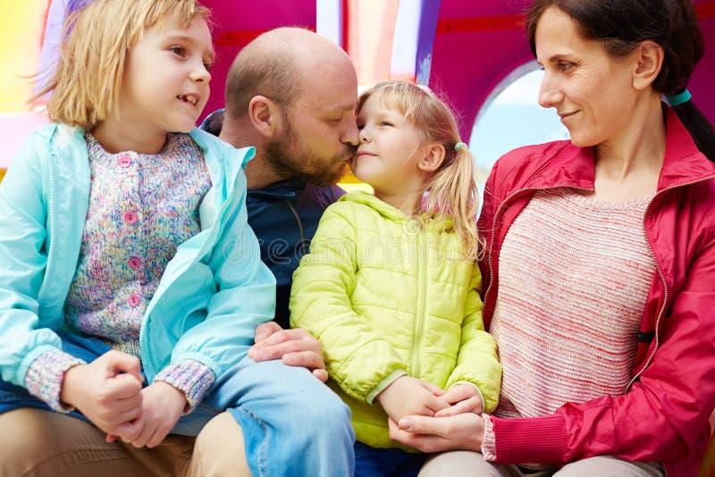 Fader som försiktigt kysser hans lilla dotter royaltyfria foton