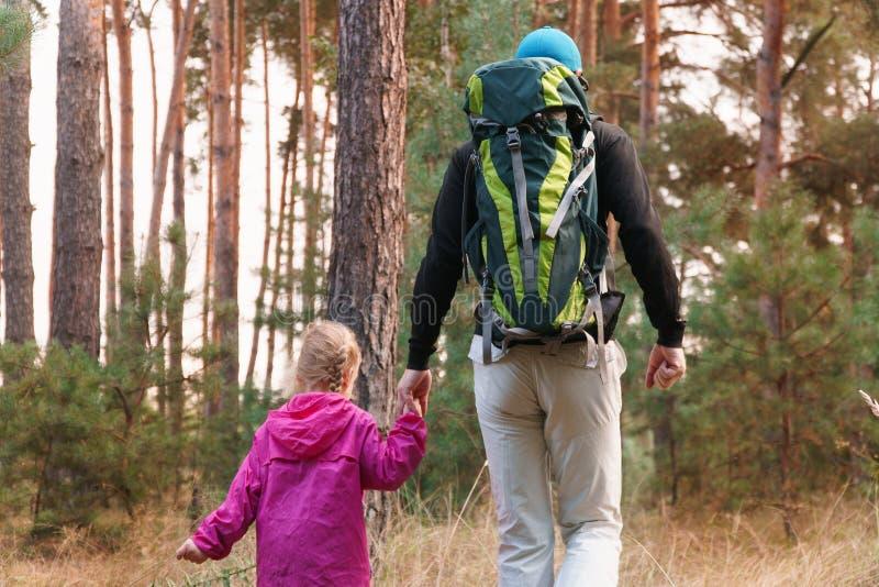Fader som fotvandrar med ungen på ryggsäcken arkivbild