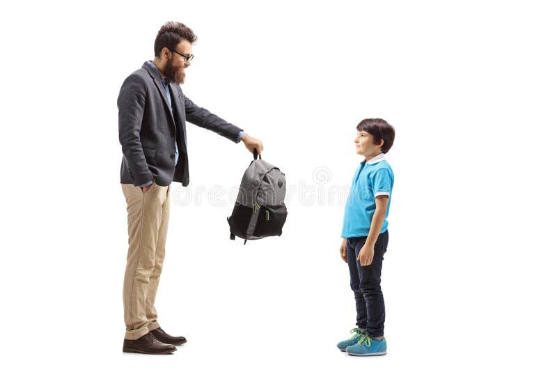 Fader som ger en ryggsäck till hans son fotografering för bildbyråer