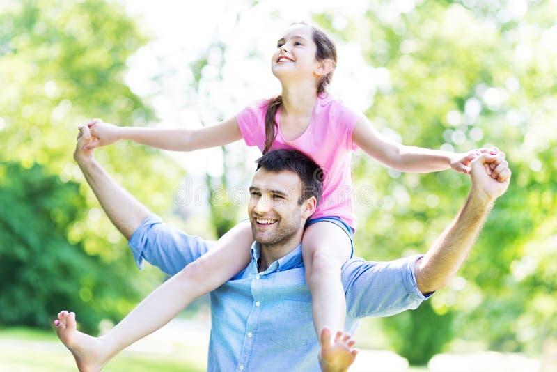 Fader som ger hans dotter en ridtur på axlarna royaltyfri fotografi