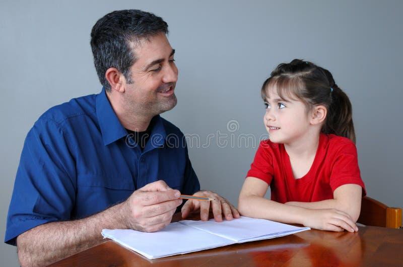 Fader som hjälper hans dotter med hennes skolaprojekt royaltyfri fotografi