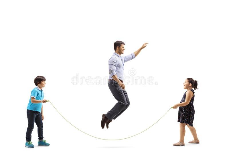 Fader som hoppar over ett rep som rymms av hans son och dotter arkivfoton