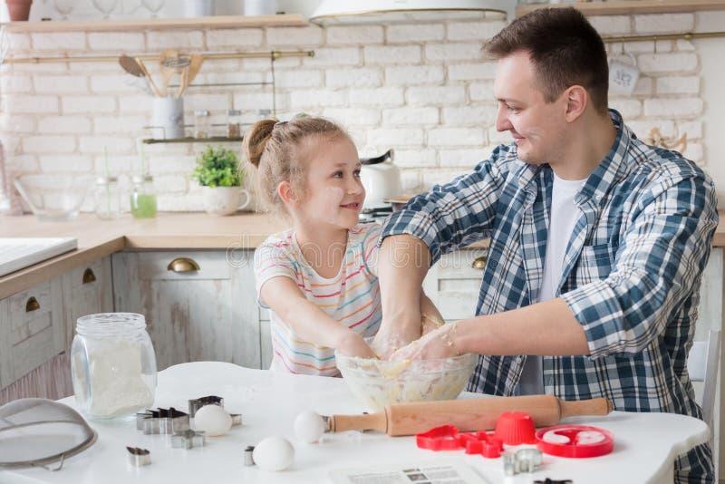 Fader som knådar deg med hans dotter som bakar i kök arkivbild