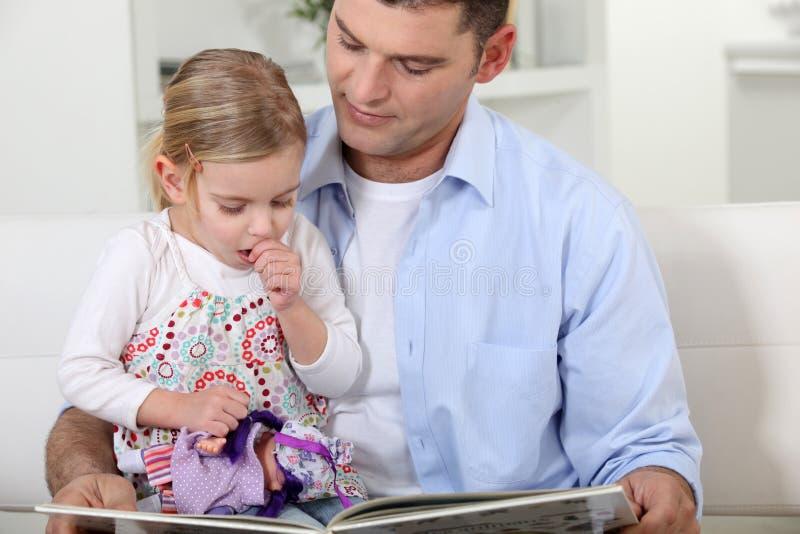 Fader som läser till hennes dotter. royaltyfri bild