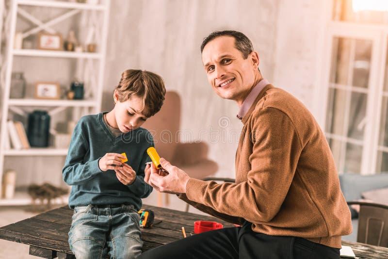 Fader som ler proudly på kameran, medan arbeta på ett projekt med hans son arkivfoton