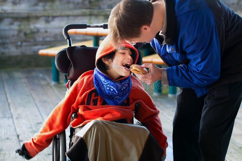 Fader som matar rörelsehindrad son en hamburgare i rullstol Barnet har royaltyfri bild