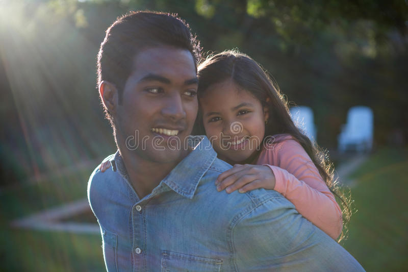 Fader som på ryggen ger ritt till hans dotter fotografering för bildbyråer