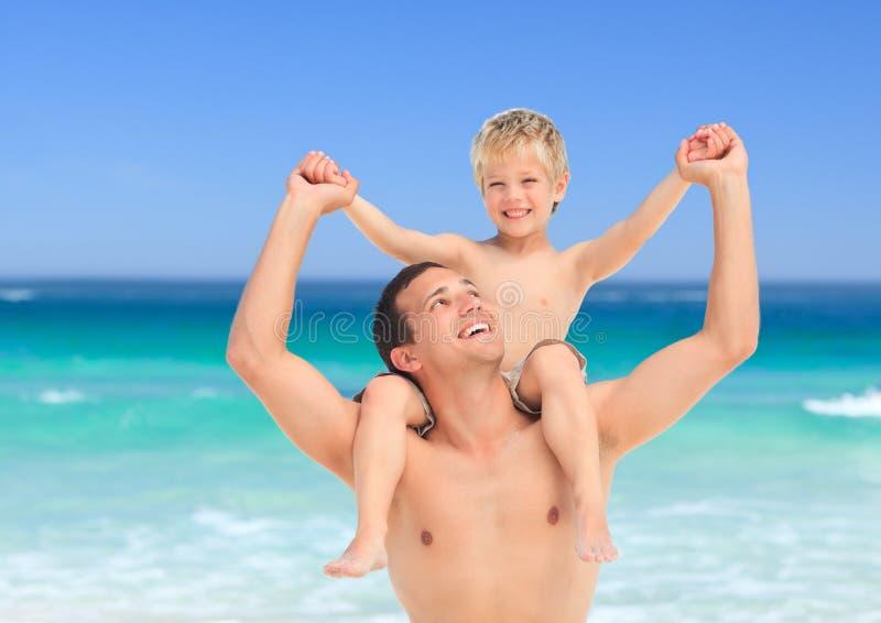fader som på ryggen ger sonen royaltyfria bilder