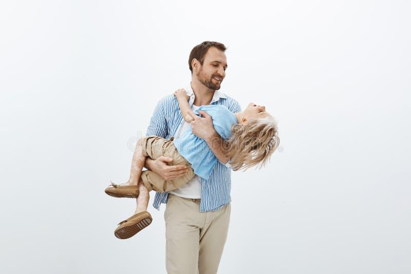 Fader som rymmer den dyrbara skatten i händer Stående av den gulliga lyckliga europeiska farsan i bärande son för tillfällig dräk royaltyfria bilder