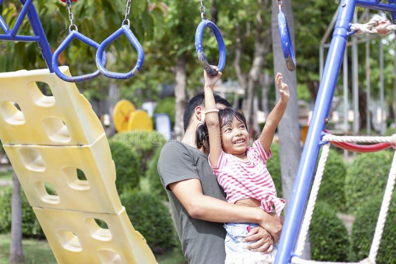 Fader som rymmer en dotter som spelar p? lekplatsen p? ferie arkivbilder