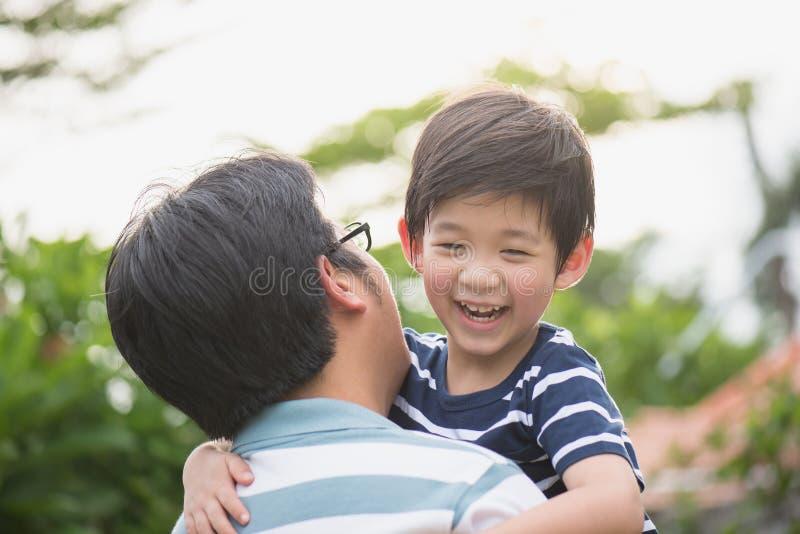 Fader som rymmer hans son i parkera arkivfoton