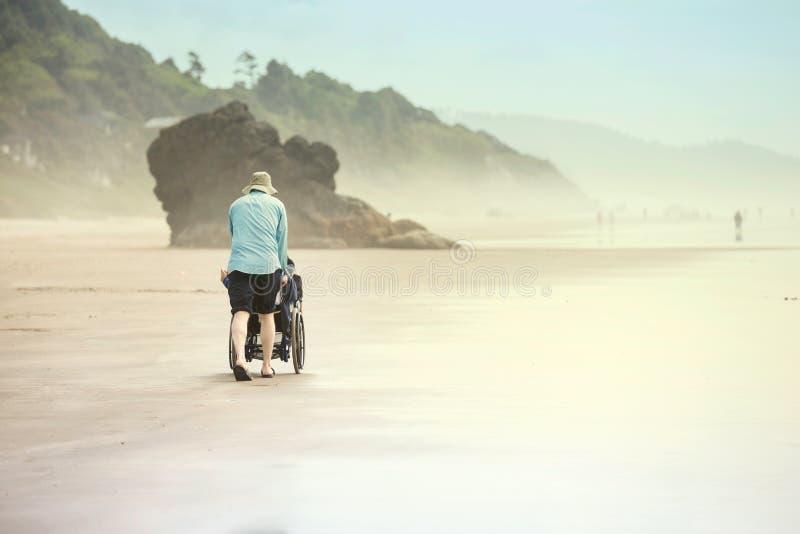 Fader som skjuter det rörelsehindrade barnet i rullstol längs den dimmiga stranden royaltyfria foton