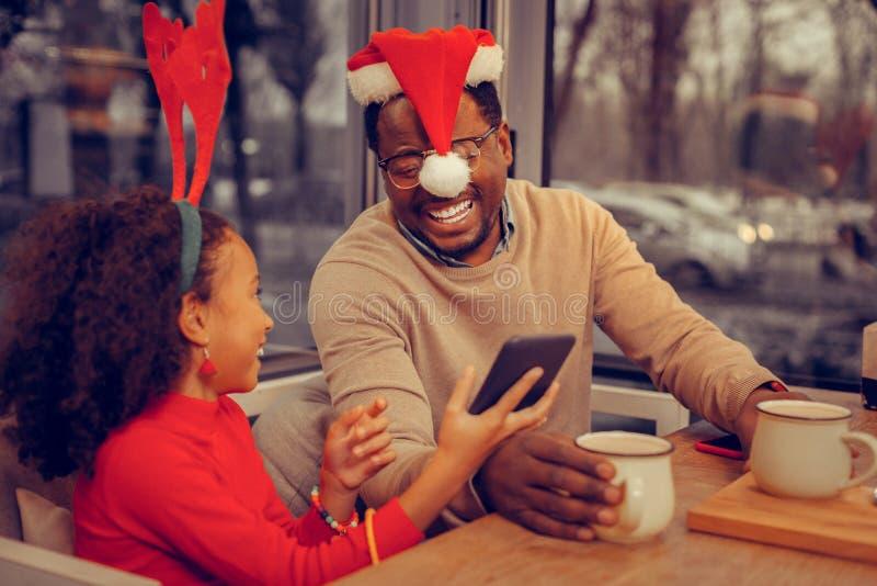Fader som skrattar, medan se julfotoet med dottern arkivbilder