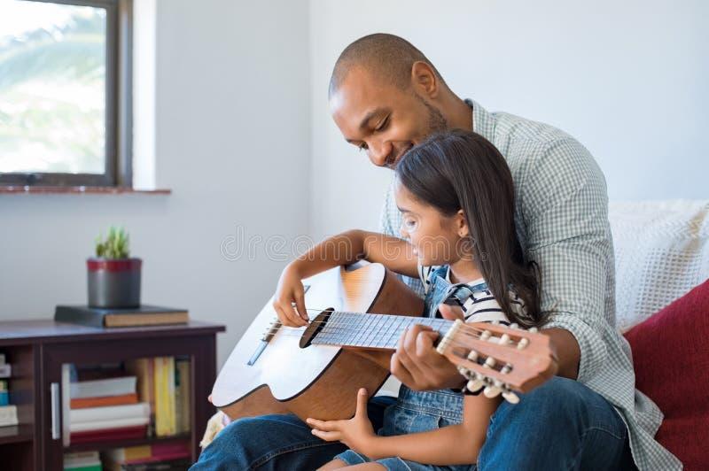 Fader som spelar gitarren med dottern royaltyfri fotografi