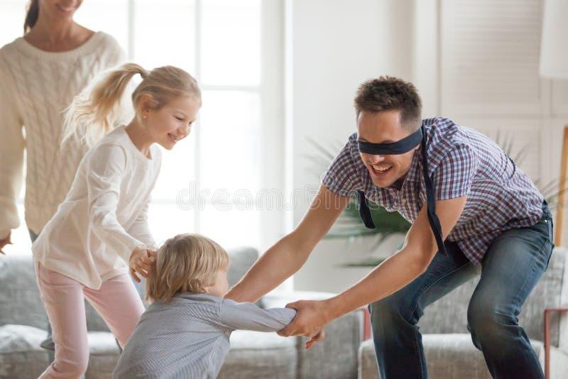 Fader som spelar kurragömmaleken med hemmastadda ungar royaltyfri bild