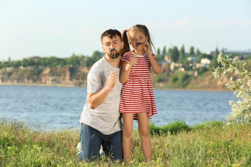 Fader som spelar med den lilla dottern på solig dag utomhus royaltyfri bild