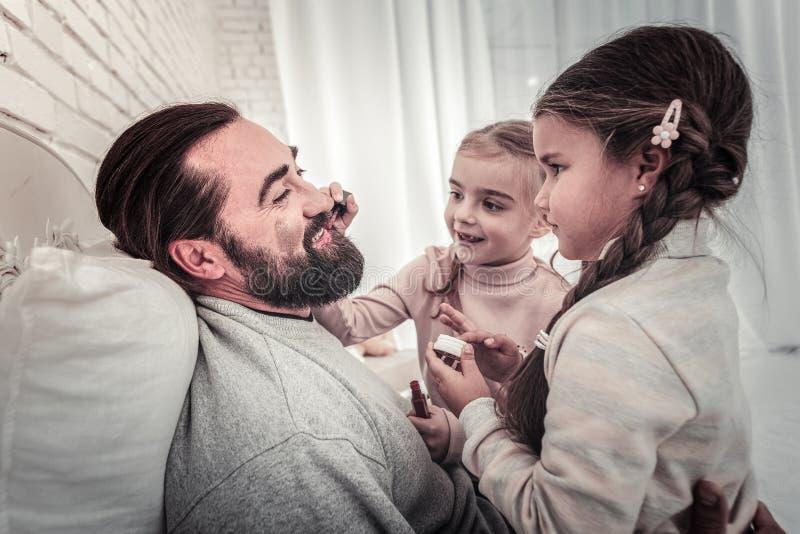 Fader som spelar med ungar, genom att låta dem måla hans framsida arkivfoton