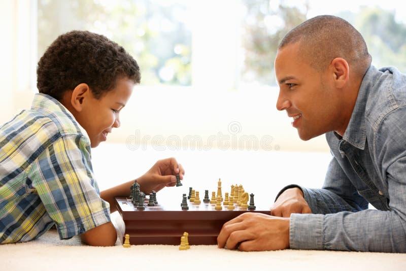 Fader som spelar schack med sonen arkivbild