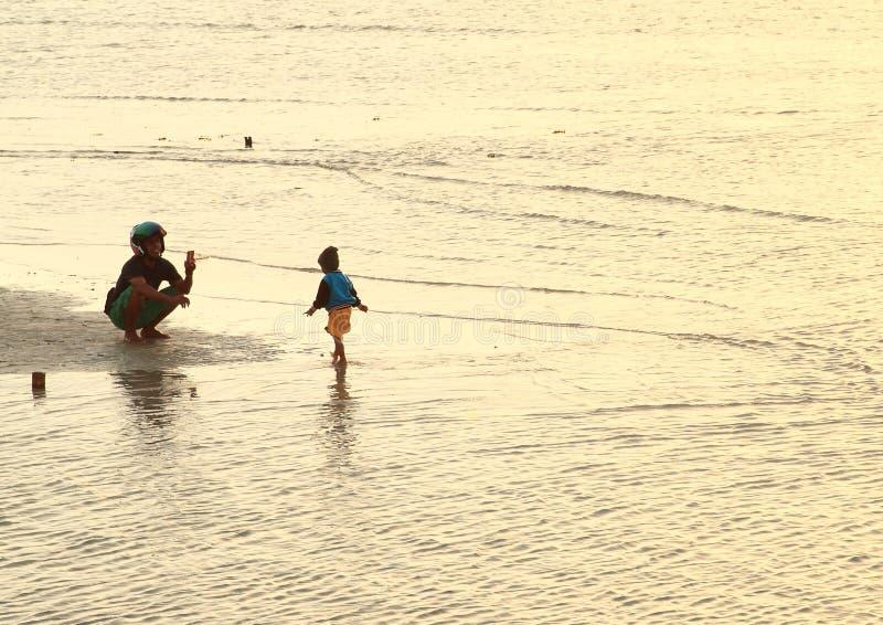 Fader som tar fotoet av sonen på stranden royaltyfria bilder