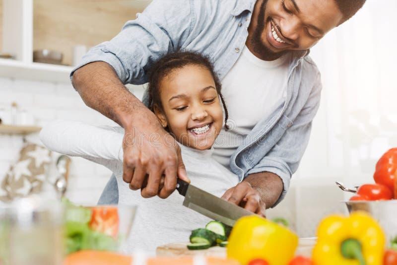Fader som undervisar hans dotter att klippa grönsaker fotografering för bildbyråer