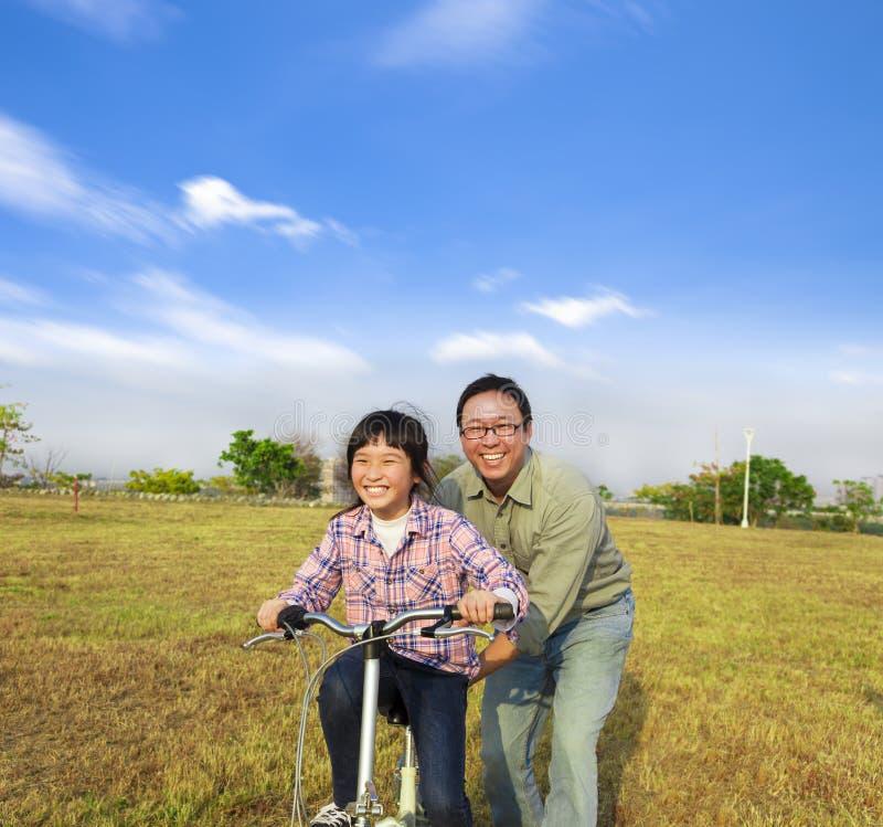 Fader som undervisar hans dotter att rida cykeln royaltyfria bilder