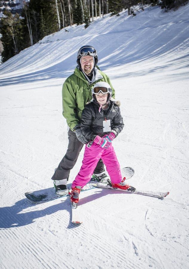 Fader som undervisar hans dotter hur man skidar royaltyfria foton