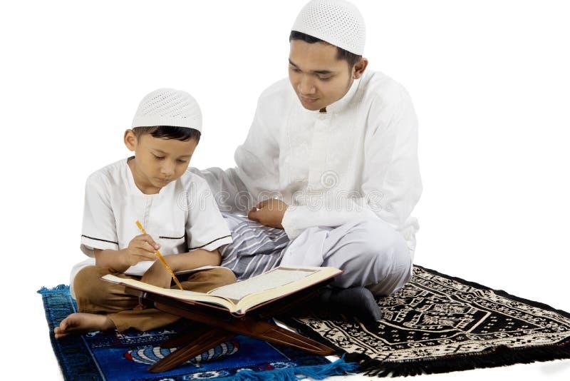 Fader som undervisar hans son läs- Quran arkivbild