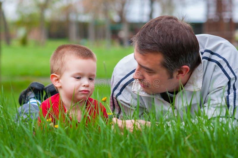 Fader som undervisar hans son om naturen royaltyfri fotografi