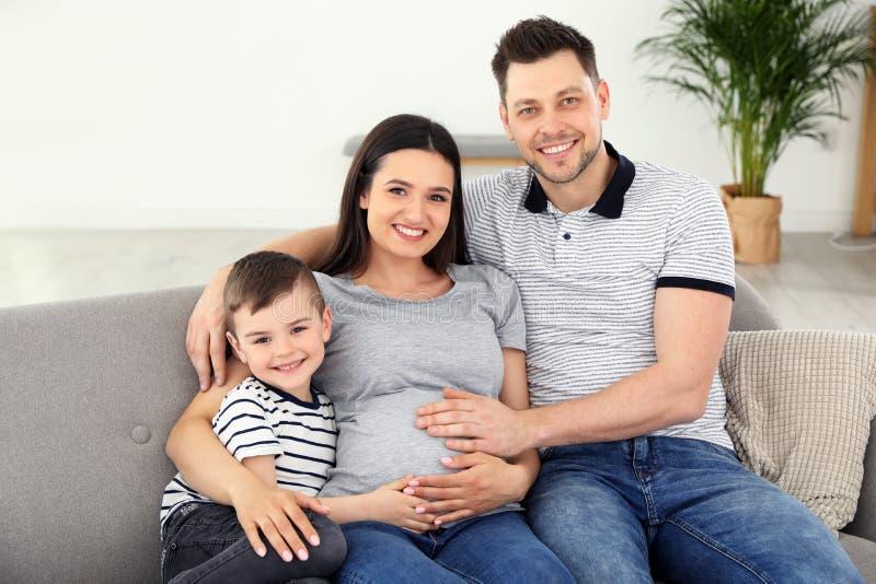 Fader, son och gravid moder som tillsammans spenderar tid på soffan Familj Tid arkivfoto
