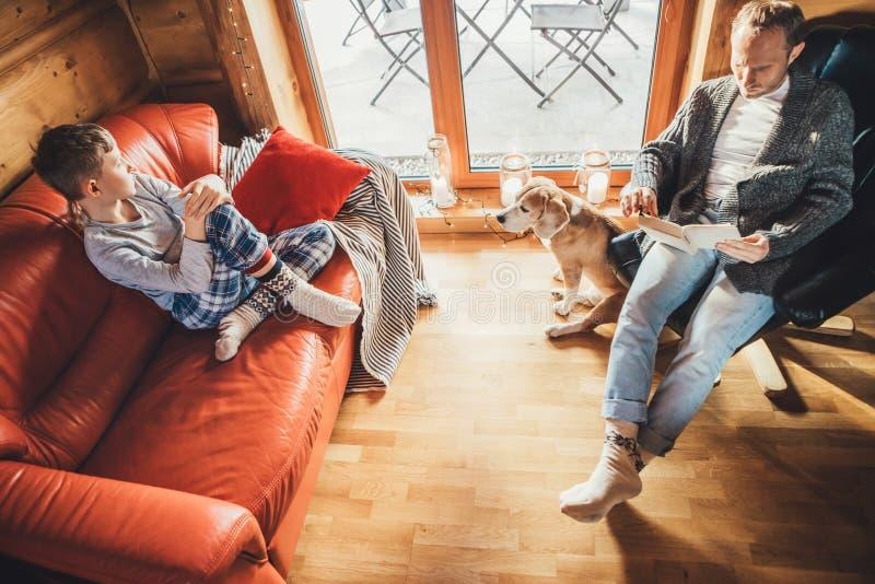 Fader, son och hans beagle hund tillbringar semester i ett glatt hus Pappa läser en bok, pojke som sitter och lyssnar, hund royaltyfri bild