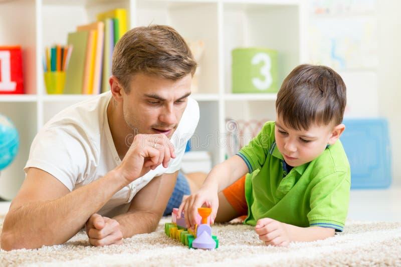 Fader And Son Playing med hemmastadda kvarter arkivfoto