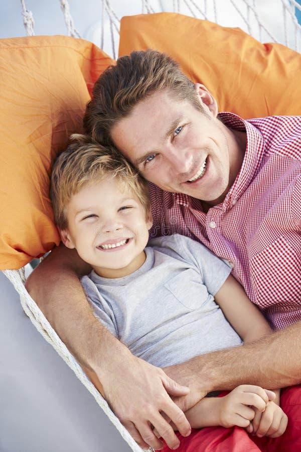 Fader And Son Relaxing i trädgårds- hängmatta tillsammans royaltyfri foto