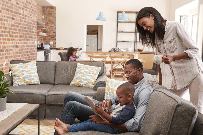 Fader And Son Sit On Sofa In Lounge som använder den Digital minnestavlan arkivbilder