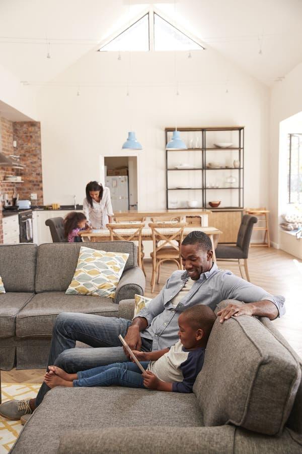 Fader And Son Sit On Sofa In Lounge som använder den Digital minnestavlan royaltyfri foto