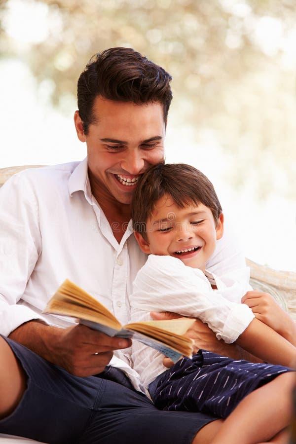 Fader And Son Sitting i trädgårds- läsebok tillsammans arkivfoto