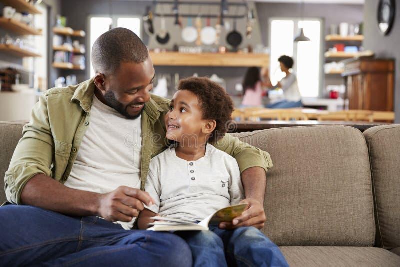 Fader And Son Sitting på Sofa In Lounge Reading Book tillsammans arkivbilder
