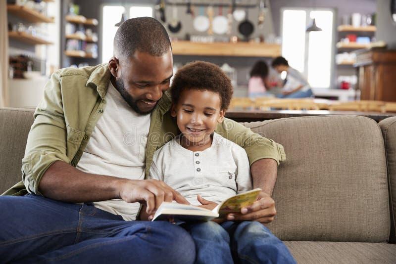Fader And Son Sitting på Sofa In Lounge Reading Book tillsammans royaltyfri foto