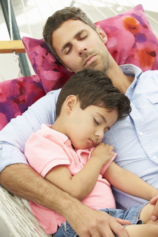 Fader And Son Sleeping i trädgårds- hängmatta tillsammans royaltyfri bild