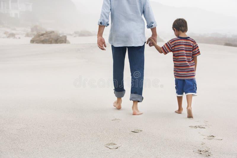 Fader And Son Walking på sand på stranden arkivbild