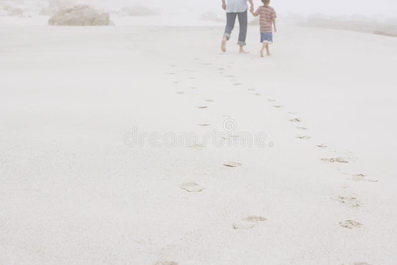 Fader And Son Walking som lämnar bak fotspår på sand royaltyfri bild